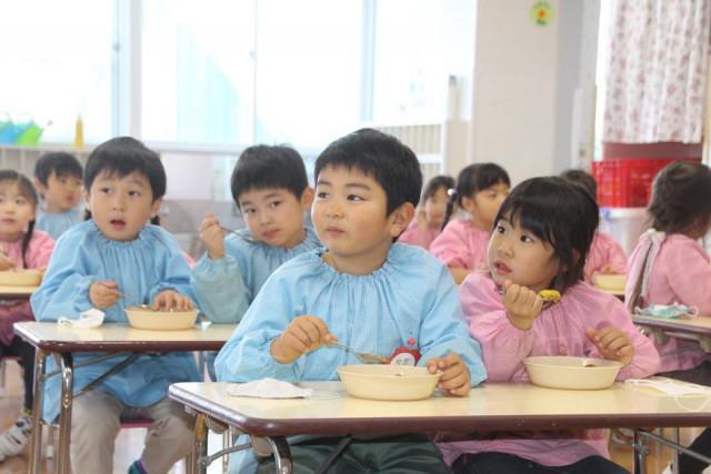 スイートポテトをおいしそうに食べる園児