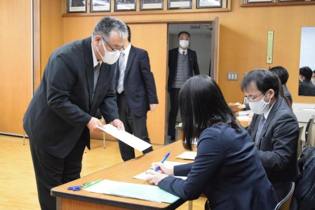 高校担当者(右)に出願書類が入った封筒を手渡す中学校教員