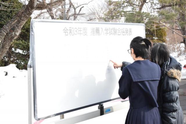 校舎前に設置した掲示板で受験番号を確認する受験生ら