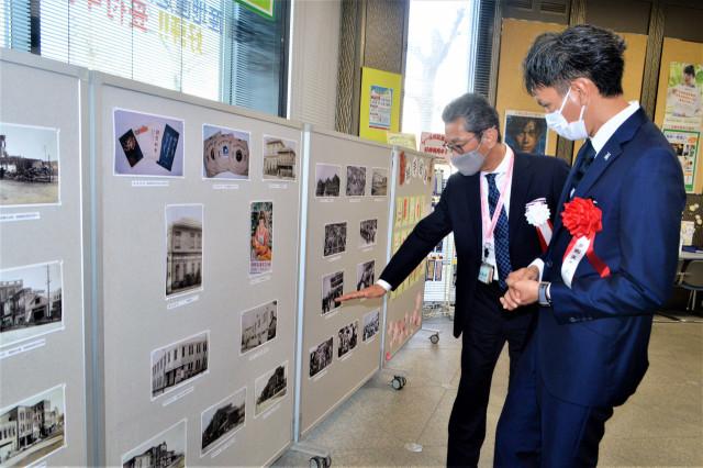 本田局長(左)から写真展の説明を聞く渡邉社長