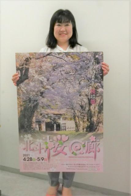 「桜回廊」ポスターを掲げる市観光協会職員