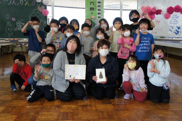 児童に囲まれる新岡教諭(前列中央左)と如意輪観音を発見した川口さん(同右)