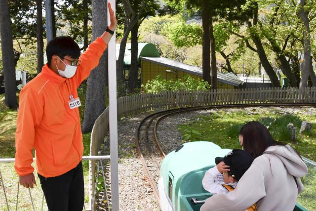 遊具の乗り方を来園者に説明する加藤さん(左)