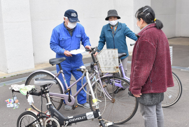 ブレーキやタイヤなど10項目を点検し、自転車の安全な利用を呼び掛ける北川さん(左)