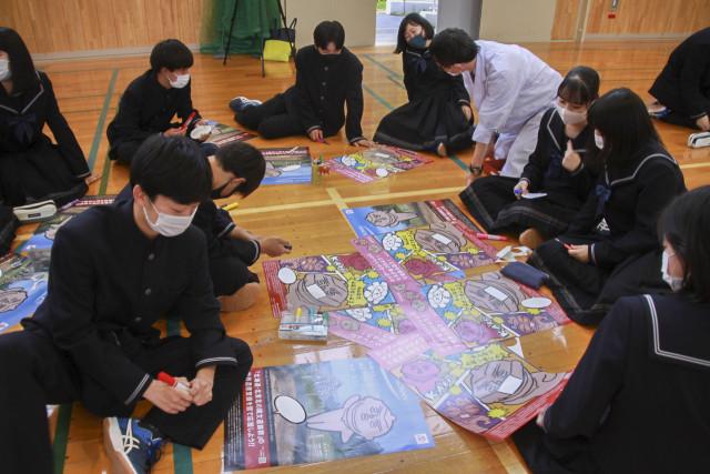 北海道・北東北の縄文遺跡群の世界文化遺産登録を応援するポスターにメッセージ入りの吹き出しを貼り付ける生徒たち
