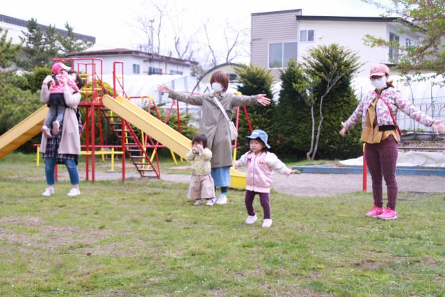 園庭で体操など体を動かしながら運動や遊びを楽しむ親子