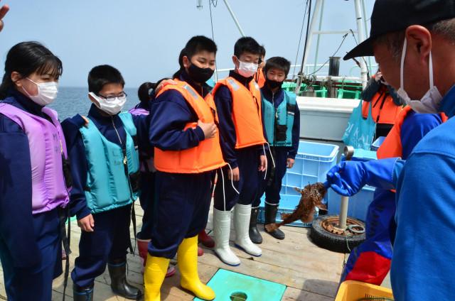 網にかかった魚の説明を受ける生徒ら