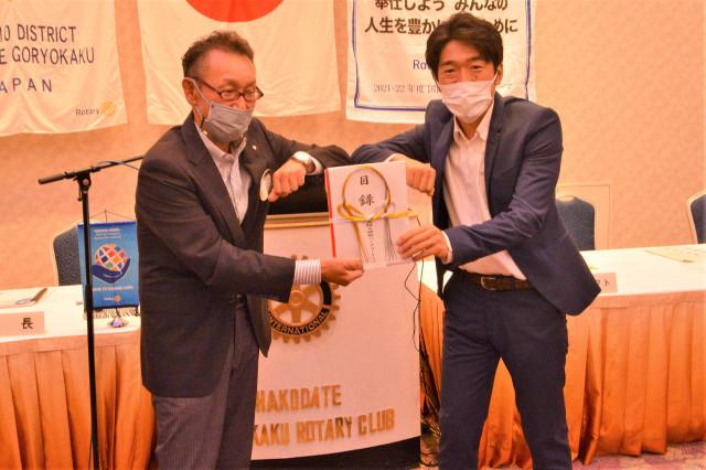 波並代表に目録を手渡す村田会長(左)