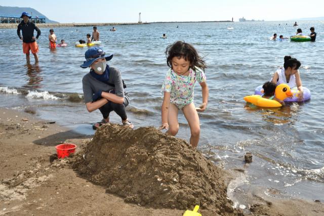 思い思いに水遊びや砂遊びを楽しむ親子連れたち