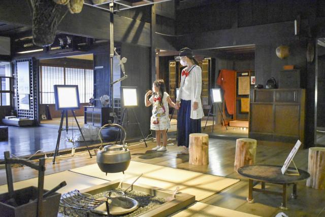 旧笹浪家住宅の落ち着いた室内で光る絵本を鑑賞する来場者(16日、上ノ国町)
