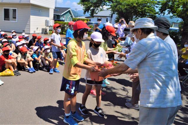 石川町会の関係者に花苗を手渡す児童