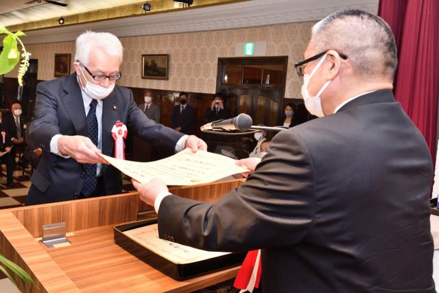 河尻支局長から表彰状を受け取る川嵜さん(左)