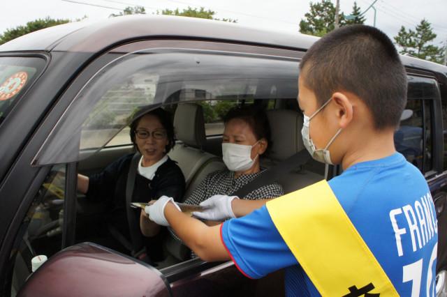 児童から交通安全グッズを受け取るドライバー