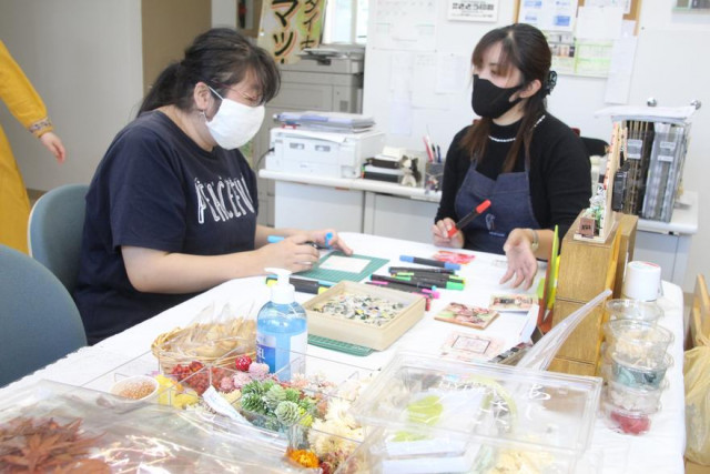 タイルアートを楽しむ参加者(左)